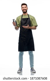 alcohol drinks, people and job concept - happy smiling barman in black apron with shaker preparing cocktail over white background