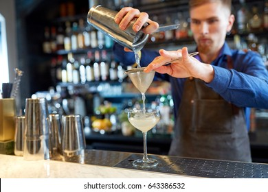 alcohol drinks, people and luxury concept - bartender pouring cocktail from shaker through strainer into glass at bar