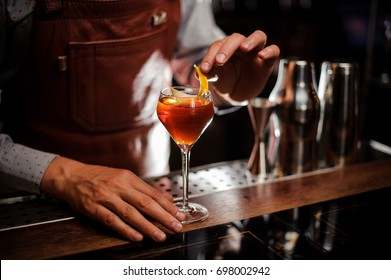 alcohol drinks, people and luxury concept - bartender with glass and lemon peel preparing cocktail at bar
