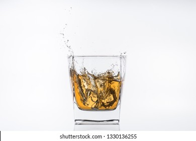 Alcohol drinks. Whiskey with ice. Rum with ice. Brown brandy with ice. Ice cube falling with splashes into a glass with alcohol