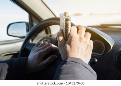 Alcohol is driving a car while driving. The hand of a drunk driver holds a flask with an alcogol at the helm of his car.