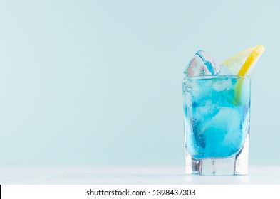 Alcohol juicy fruit blue cocktail with curacao liquor, lemon slice, ice cubes in frozen shot glass in modern elegant pastel blue interior.