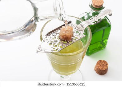 Alcohol, luxurious spirits and dangerous liquor conceptual idea with crystal glass of absinthe, pouring water on stainless steel spoon, sugar cube and green bottle of strong spirit on white background