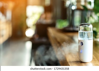 Alcohol nano mist sprayer for hand cleaning to prevent the spread of the corona virus (Covid-19) placed on the table to serve customers before buying in the coffee shop. Modern health technology.