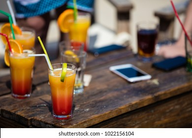 Alcohol orange daiquiri and cuba libre cocktail on beach bar rustic wooden table.