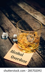 alcohol overdose with label on paper note. Glass of scotch whiskey