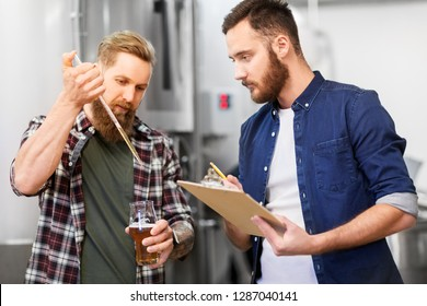 alcohol production, manufacture, business and people concept - male brewers with pipette and clipboard testing craft beer at brewery