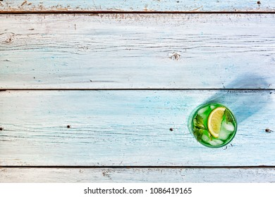 alcohol. Refreshing mint cocktail mojito with rum and lime, cold drink or beverage with ice on white wooden background, top view