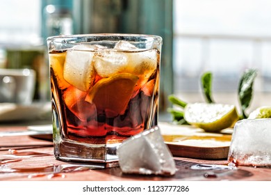 alcohol, rum, coctail cuba libra, rum and cola cuba libre with lime and Ice into the glass beaker closeup