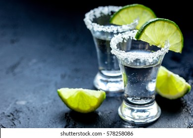 Alcohol shots with lime and salt on black background