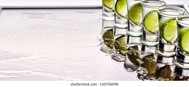 alcohol. Tequila shot with lime, sea salt and ice, party, selective focus, top view, copy space