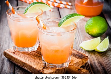 Alcohol tequila sunrise cocktail with ice and lime