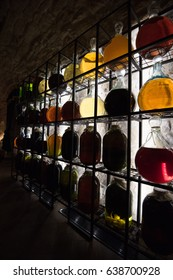 Alcohol in vintage large bottles is placed on decorative racks with darkened illumination.