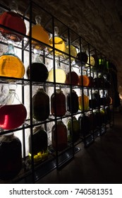 Alcohol in vintage large bottles is placed on decorative racks with vibrant illumination.