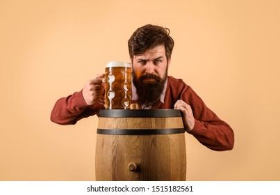 Alcohol. Wooden barrel. Glass of beer. Celebration Oktoberfest. Serious bearded man with glass beer. We meet oktoberfest. Germany traditions. Beer pub and bar. Brewery concept. Man tasting draft beer.