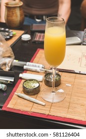 Alcoholic beverage in focus, on table place mat near cannibus and related accessories.