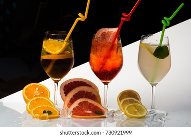 Alcoholic beverage and fruit at restaurant. Party and summer vacation. Cocktails on black background. Drink and food. Fruit slice and cocktail glass at bar.
