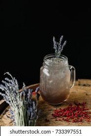 An alcoholic beverage garnished with lavender on dark background