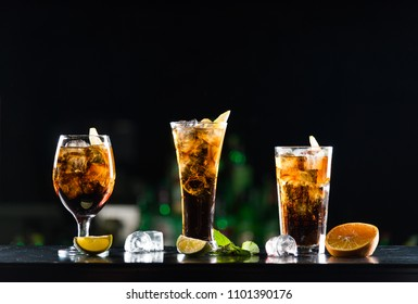 Alcoholic beverages whiskey and cola in glasses of different shapes on the bar table.