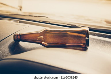 An alcoholic bottle on a car console / Drunk driving concept