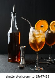 Alcoholic cocktail Aperol Spritz in a wine glass covered with water drops, slice of orange ,ice cubes and metal straw on dark background