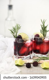 Alcoholic cocktail. Cold alcohol drink with ice, lime, blackberry and gin, decorated of rosemary.