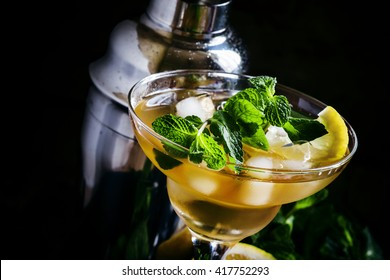 Alcoholic cocktail daiquiri with lemon and mint, dark background, selective focus