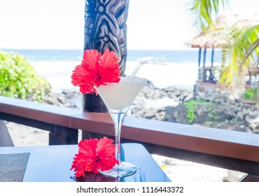 Alcoholic cocktail drink with red hibiscus flower garnish with wooden carving in background at beach bar on Upolu Island, Western Samoa, South Pacific
