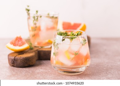 Alcoholic cocktail gin bitter lemon with thyme and grapefruit. Fruit lemonade. Gray slate background. Horizontal view. Copy space