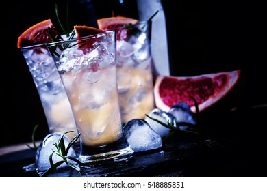 Alcoholic cocktail with grapefruit juice, crushed ice, vodka and rosemary, night neon light, black stone background, selective focus