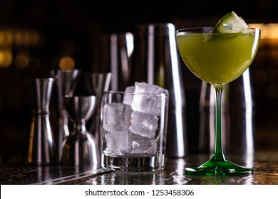 Alcoholic cocktail of green color on a bar counter. Cucumber cocktail.