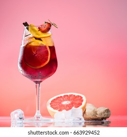 alcoholic cocktail Jager bomb with cinnamon sticks, strawberry and grapefruit in wine glass on pink background with copy space for text