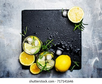 Alcoholic cocktail with lemon, vodka, soda, ice and rosemary, grunge stone background, top view