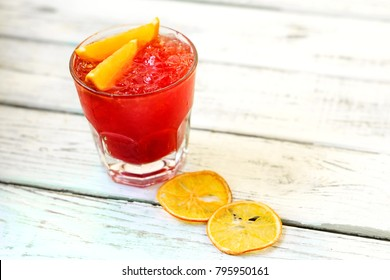 Alcoholic Cocktail made of Campari, gin, rum with orange slices and ice on white background