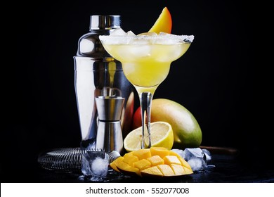 Alcoholic cocktail mango daiquiri with white rum, liqueur, syrup, lemon juice and ice cubes. Bar tools. Dark background, selective focus