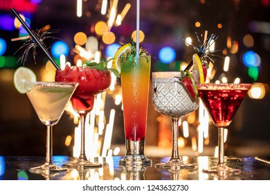 Alcoholic cocktail row on bar table, colorful party drinks.