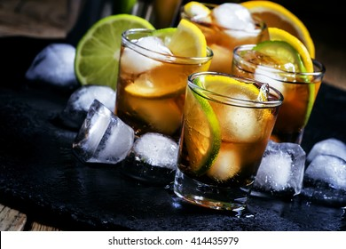 Alcoholic cocktail rum cola with ice, lime, lemon, cola and white rum, dark background, selective focus