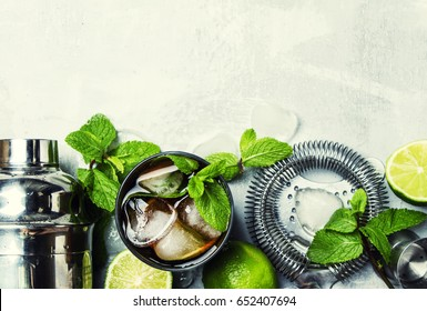 Alcoholic cocktail with rum, cola, ice and mint, bar tools, drink background, top view