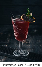 Alcoholic cocktail. Rum, peach liquor, cherry juice. On a black wooden background