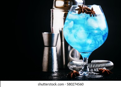 Alcoholic cocktail with sambuca, liqueur, lemon juice, crushed ice and stars of anise, black background, selective focus