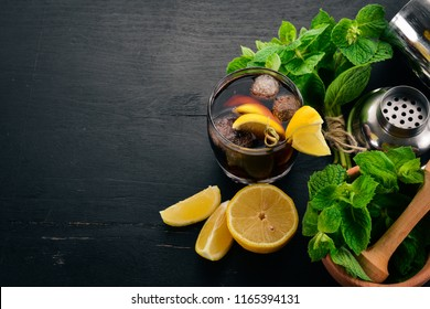 Alcoholic cocktail of whiskey, lemon and mint. Rum-Cola. Brandy. On a black wooden background. Free space for text.