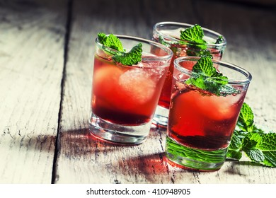 Alcoholic cocktail with white rum Bacardi, Campari, vermouth, mint and ice cubes, vintage wooden background, selective focus