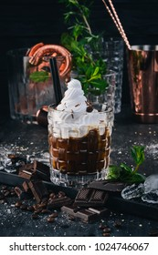 Alcoholic cocktail White Russian. Coffee Liqueur On a black wooden background.