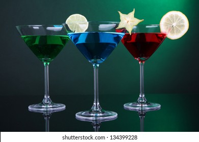 Alcoholic cocktails in martini glasses on dark green background