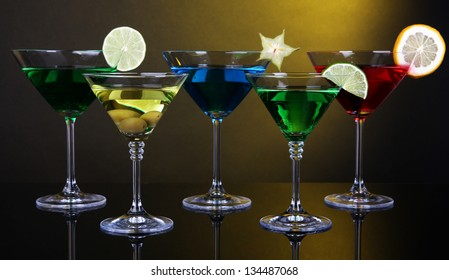Alcoholic cocktails in martini glasses on dark yellow background