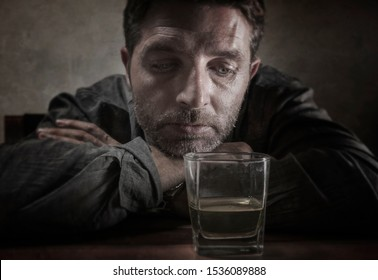 alcoholic depressed and drunk addict man sitting in front of whiskey glass trying holding on drinking in dramatic expression suffering alcoholism and alcohol addiction on isolated background
