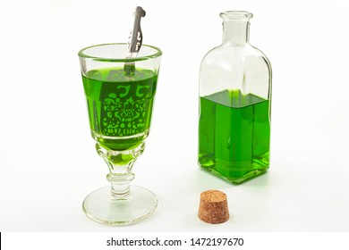 Alcoholic drink derived from botanical plants concept theme with vintage glass, metal spoon and retro looking bottle isolated on white background