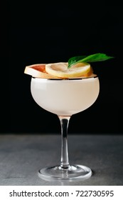 Alcoholic drink garnished with blood orange and basil on dark background basil on dark background with negative space