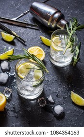 Alcoholic drink gin tonic cocktail with lemon, rosemary and ice on stone table.