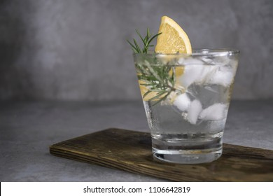 Alcoholic drink gin tonic cocktail with lemon, rosemary and ice on table.